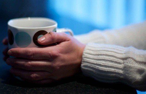 Hands holding mug of hot liquid, white jumper visible