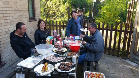 People smiling around a full picnic table of BBQ food