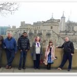Hostel residents stand in front of the Tower of London