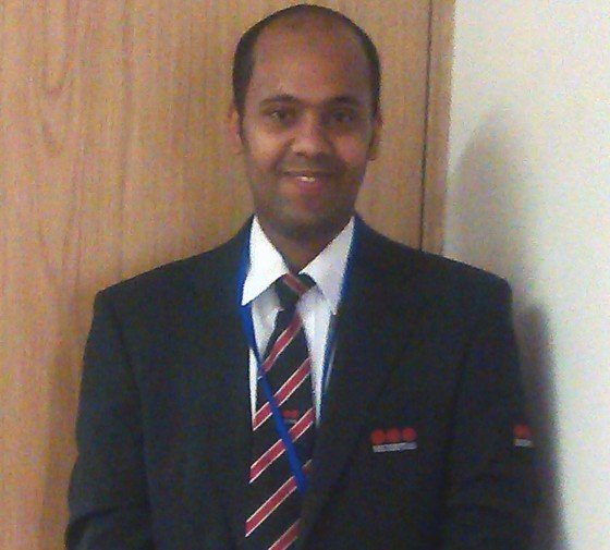Amal smiling in a suit ready to go to work