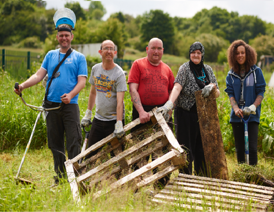 Supported living residents clearing an allotment space in Huddersfield