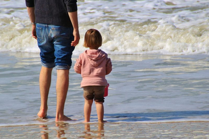 Man and small child stand on the seashore