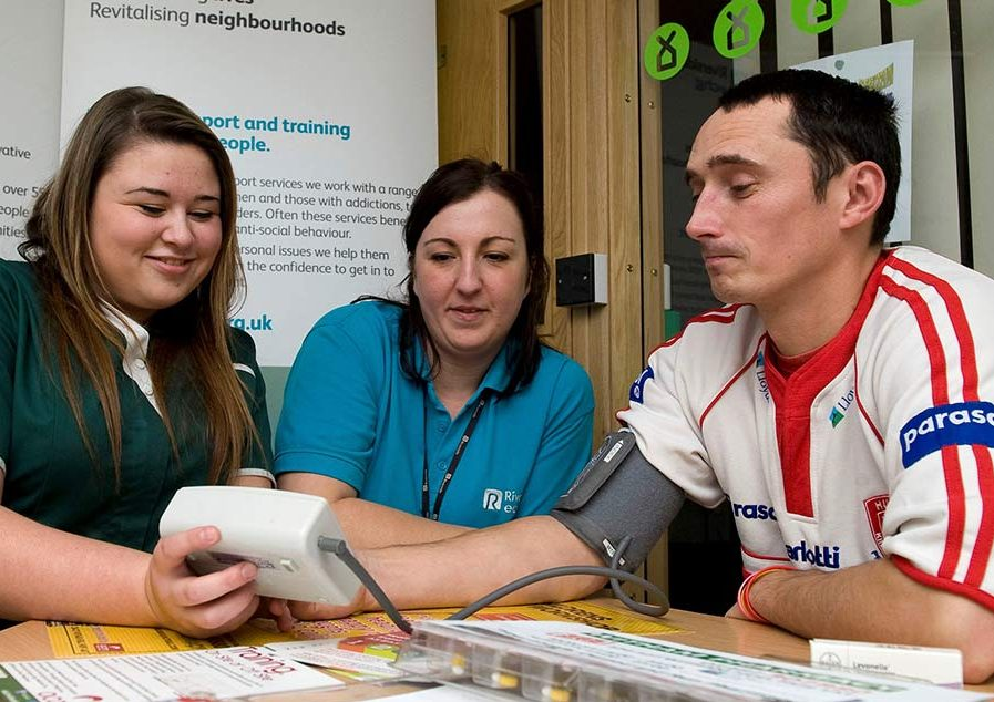 A nurse and staff member test a homelessness scheme resident's blood pressure during a health and wellbeing open day