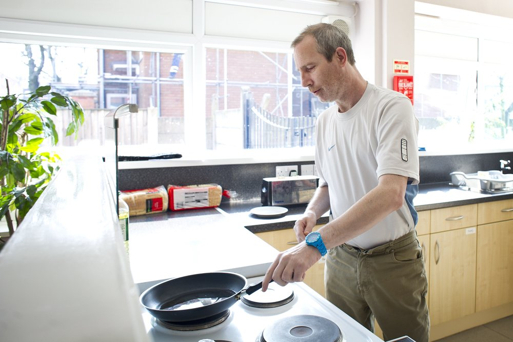 Man frying eggs at a cooking lesson