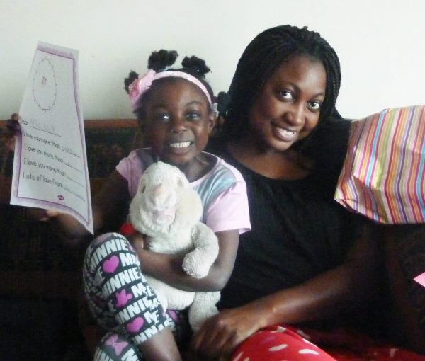 Little girl gives her mum a Mother's Day card and presents