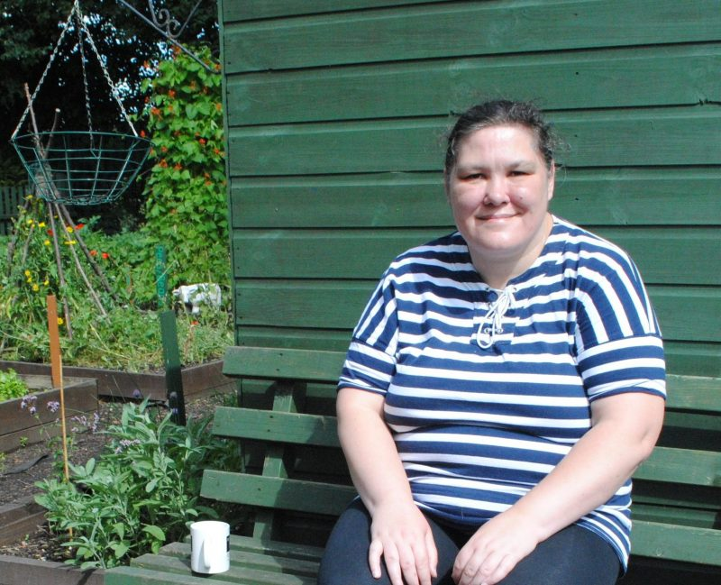 Elaine sits on a bench in the hostel garden that gave her her confidence back