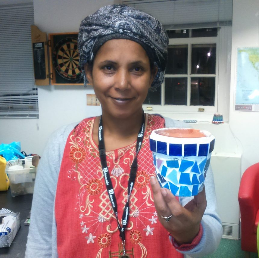 Mosaic making at women's hostel - woman holding a personalised pot