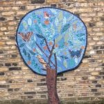Mosaic of tree on the wall at Queen Mary's hostel