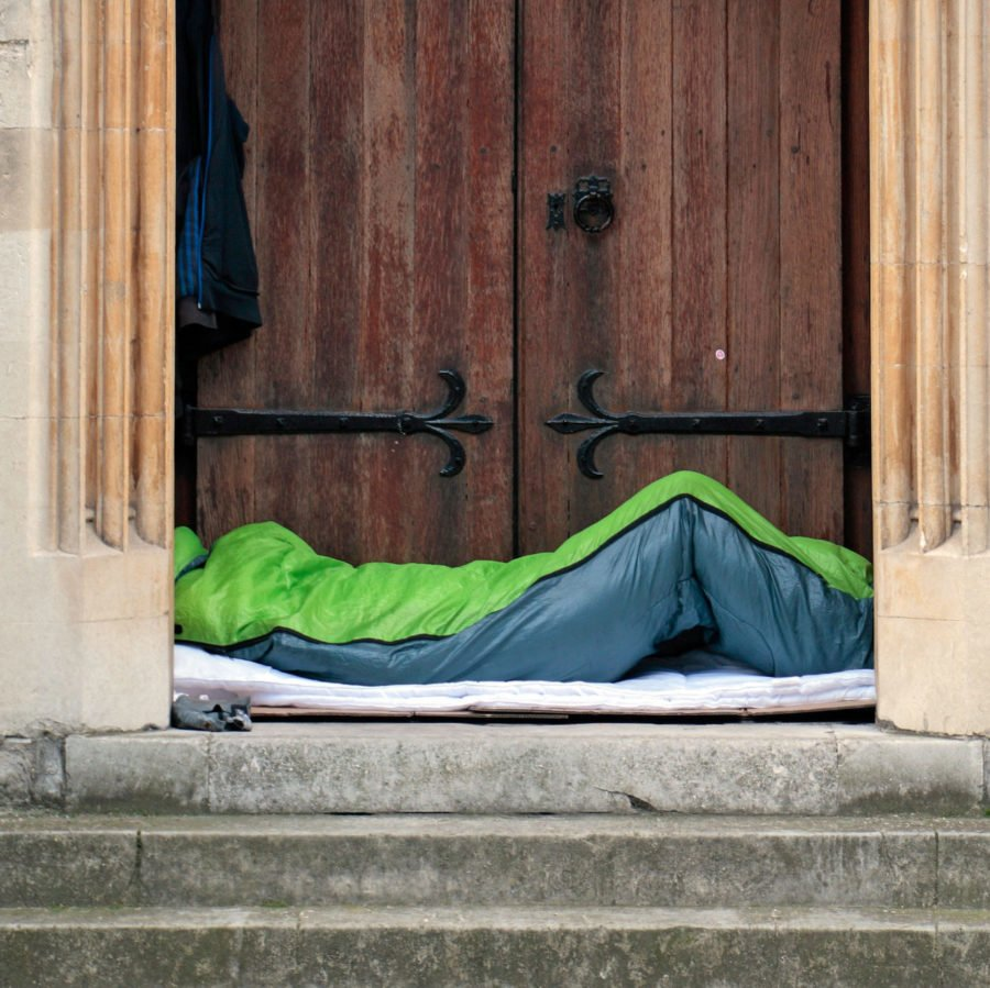 A man sleeping in a sleeping bag in a church doorway in London, UK