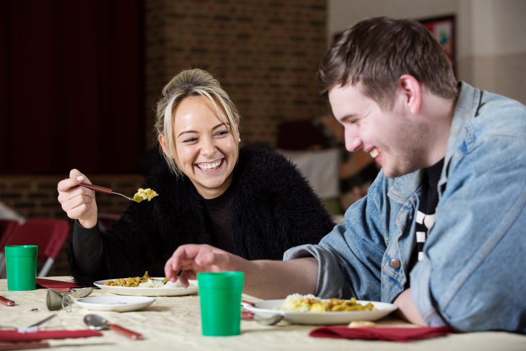 Two people eating together at a church winter night shelter