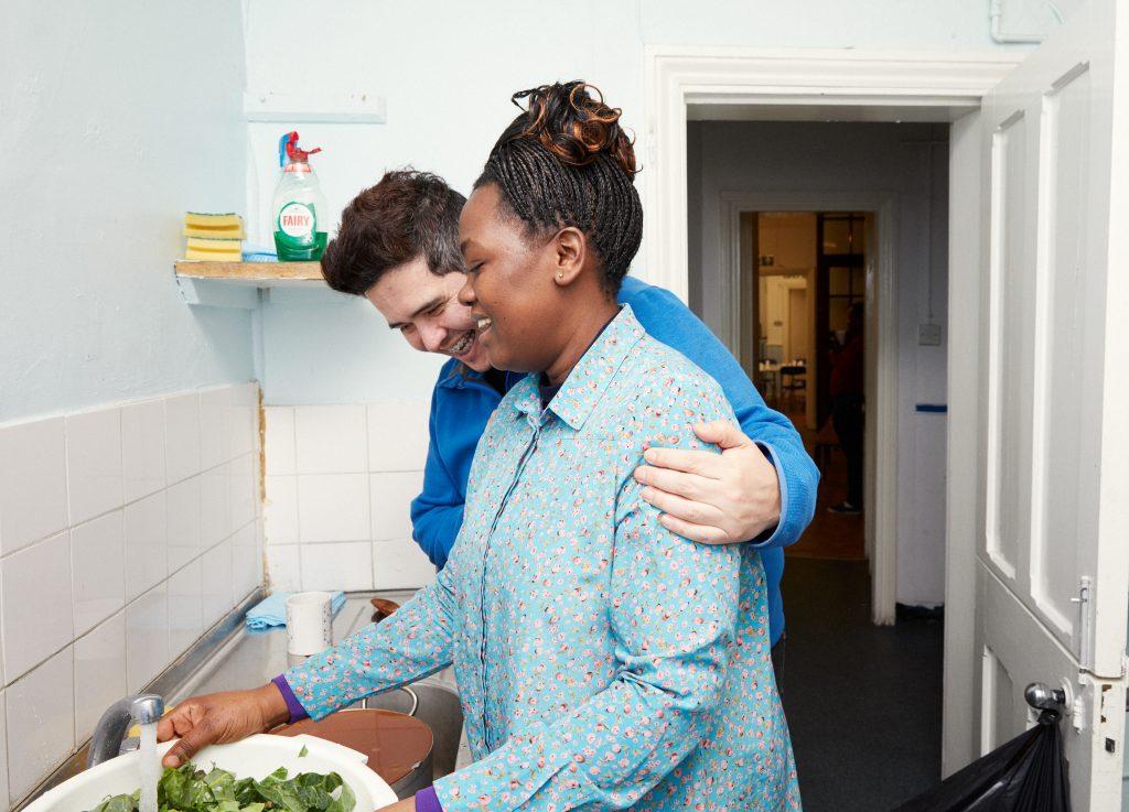 Two shelter volunteers preparing food